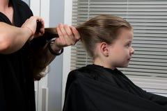 El estilista recoge, pelo apretado de la cola muchachas para crear una nueva imagen del pelo imagenes de archivo
