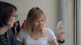 El estilista selecciona las muestras de los colores del maquillaje para las mujeres rubias dentro del plano metrajes