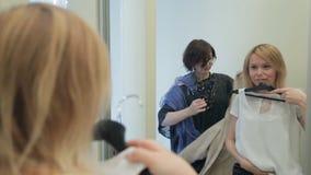 El estilista selecciona un sistema de ropa casual a las mujeres almacen de metraje de vídeo