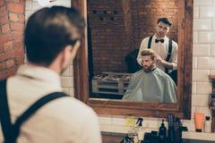 El estilista vestido con clase hermoso de la peluquería de caballeros está presentando el re fotografía de archivo