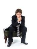 Muchacho joven que se sienta en silla Foto de archivo libre de regalías
