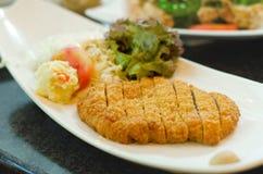 El estilo japonés frió el cerdo con los purés de patata en la placa blanca Imagenes de archivo