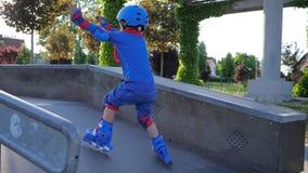 El estilo libre, el niño en casco y el traje participa en competencias en rollerdrome almacen de video