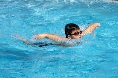 El estilo sano de la mariposa del muchacho nada en piscina Imagenes de archivo