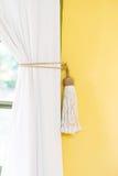 El estilo simple de la cortina del lazo-detrás de la decoración blanca del hogar dentro amarillea la pared Foto de archivo