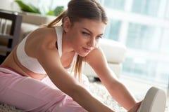 El estirar de la mujer joven, calentando, resuelve ejercicios en casa Imagenes de archivo
