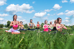 El estirar de las mujeres jovenes, calentando en clase de aeróbicos, resuelve al aire libre Imagenes de archivo