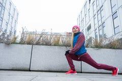 El estirar deportivo de la muchacha al aire libre en la calle de la ciudad Fotografía de archivo