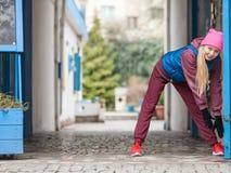 El estirar deportivo de la muchacha al aire libre en la calle de la ciudad Imagen de archivo