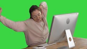 El estirar que se sienta relajado feliz delante del ordenador en una pantalla verde, llave de la mujer joven de la croma almacen de metraje de vídeo