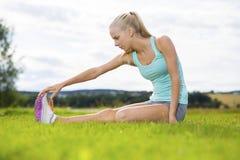 El estirar rubio apto de la mujer al aire libre en la hierba Foto de archivo