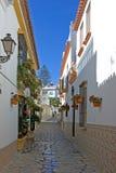 El estrecho cobbled la calle posterior colorida en Estepona España Fotografía de archivo