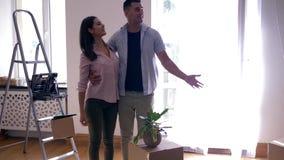 El estreno de una casa, los amantes jovenes viene en y mira el nuevo plano después de la renovación con las cajas de cartón y las metrajes