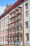 El estuco y la pintura con el andamio trabaja durante la pared exterior Imagenes de archivo