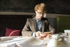 El estudiante adolescente masculino moderno joven trabaja con PC y los libros de la tableta en día soleado brillante en restauran Fotografía de archivo libre de regalías