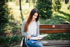 El estudiante adulto joven atractivo en banco al aire libre leyó el libro en parque Fotografía de archivo libre de regalías