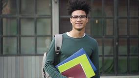 El estudiante afroamericano confiado se está colocando en el frente del campus almacen de video