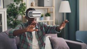 El estudiante afroamericano se está divirtiendo con los vidrios de la realidad virtual que ponen en el dispositivo y los brazos m almacen de video