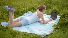 El estudiante agradable Girl está estudiando en parque con el inSummer del ordenador portátil y del cuaderno en hierba metrajes