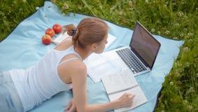 El estudiante agradable Girl está mintiendo en parque con el ordenador portátil y el cuaderno en verano metrajes
