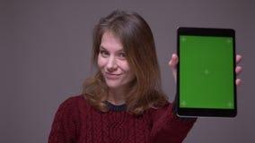 El estudiante alegre enciende el app en la tableta y demuestra la pantalla verde de la croma en fondo gris metrajes