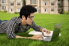 El estudiante aprende con el ordenador portátil en el parque Imagen de archivo libre de regalías