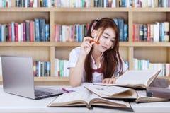 El estudiante aprende con los libros en biblioteca Foto de archivo libre de regalías
