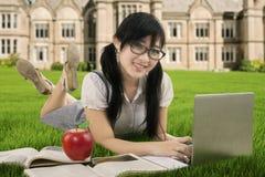 El estudiante asiático hermoso aprende en el campo Foto de archivo