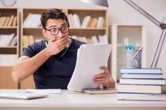 El estudiante asustado con papeleo en biblioteca Imagen de archivo libre de regalías