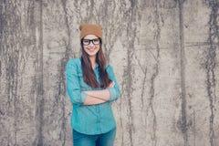 El estudiante atractivo de la chica joven se está colocando en el ` s del muro de cemento Foto de archivo