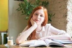 El estudiante atractivo joven de la muchacha con la piel blanca y el pelo rojo largo es libros de lectura, estudiando, rodeado po imagenes de archivo