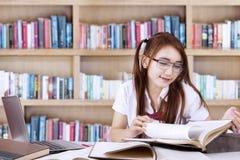 El estudiante bastante adolescente aprende en biblioteca Imagenes de archivo