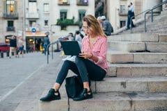 El estudiante bonito adorable se sienta en las escaleras con el ordenador portátil Fotos de archivo