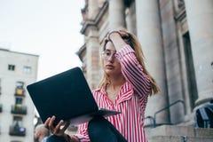 El estudiante bonito adorable se sienta en las escaleras con el ordenador portátil Imágenes de archivo libres de regalías