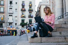 El estudiante bonito adorable se sienta en las escaleras con el ordenador portátil Foto de archivo