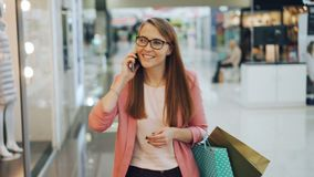El estudiante bonito está hablando con los amigos en el teléfono móvil y está disfrutando de la conversación que caminan en lleva almacen de metraje de vídeo