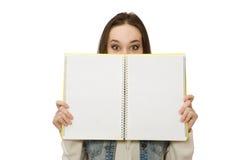 El estudiante bonito que sostiene el cuaderno en blanco aislado en blanco Imagenes de archivo