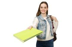 El estudiante bonito que sostiene los libros de texto aislados en blanco Imagen de archivo libre de regalías