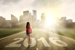 El estudiante camina en el camino con los números 2016 Foto de archivo libre de regalías