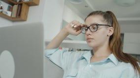 El estudiante cansado del adolescente está mecanografiando en el ordenador portátil en casa, preparándose para los exámenes o la  almacen de video