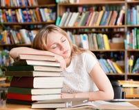 El estudiante cansado duerme en biblioteca en los libros de la pila Foto de archivo libre de regalías