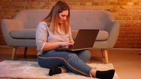 El estudiante caucásico gordo se sienta en piso que mecanografía atento en el ordenador portátil que está pensativo en atmósfera  metrajes