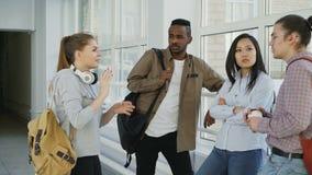 El estudiante caucásico hermoso joven se está colocando delante de sus tres groupmates multi-étnicos que discute algo almacen de video
