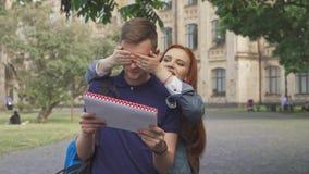 El estudiante cierra sus ojos del ` s del amigo en campus almacen de video