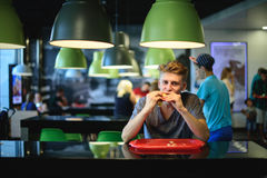 El estudiante codicioso come una gran hamburguesa hermosa que se sienta en un restaurante de los alimentos de preparación rápida Fotografía de archivo