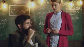 El estudiante comunica con el profesor en el tablero El compañero de clase educa concepto de la lección del conocimiento del amig metrajes