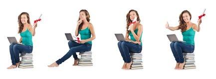 El estudiante con el netbook que se sienta en los libros Fotos de archivo