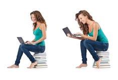 El estudiante con el netbook que se sienta en los libros Fotos de archivo libres de regalías