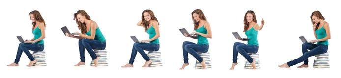 El estudiante con el netbook que se sienta en los libros Imagen de archivo libre de regalías