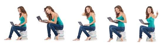 El estudiante con el netbook que se sienta en los libros Imagen de archivo